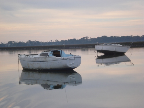 Photo by Cyrus Buffum/Charleston Waterkeeper:  Two abandoned boats litter the waters of Charleston, behind Folly Beach