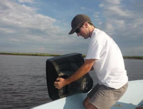 Cyrus Buffum, the Charleston Waterkeeper, pulls a floating T.V. out of the Stono River on Sunday. Photo by: Persis Buffum.